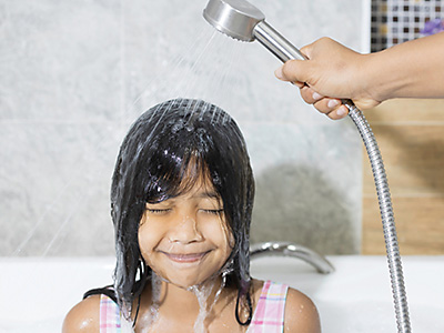Young girl sitting in bath while mum holds handheld shower head to wash her face and eyes